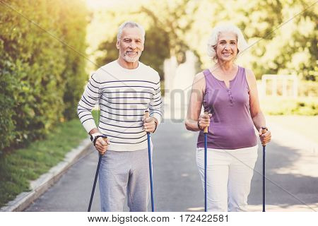 Active lifestyle. Cheerful positive elderly couple holding poles and walking with them along the park while keeping fit