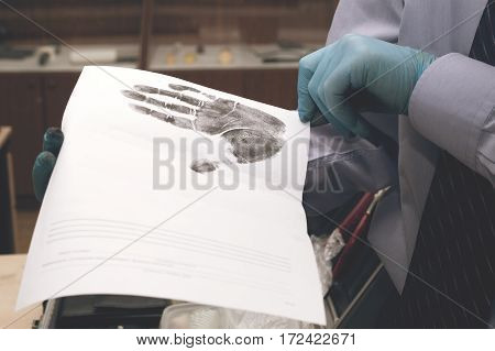 Expert Looks At The Paper With The Imprint Of His Hands. Investigation Of The Crime.