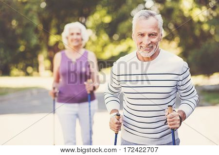 Pleasant emotions. Handsome delighted senior man holding the walking poles and smiling while looking at you