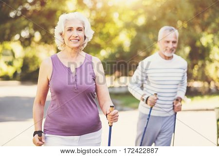 Outdoor exercises. Positive senior grey haired woman smiling and holding a pole while working out in the park with her husband
