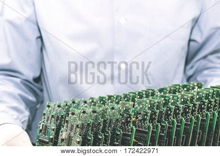 Technician with computer circuit board with chips. Spare parts and components for computer equipment. Production of electronics and maintenance. The concept of high technology and robotics.