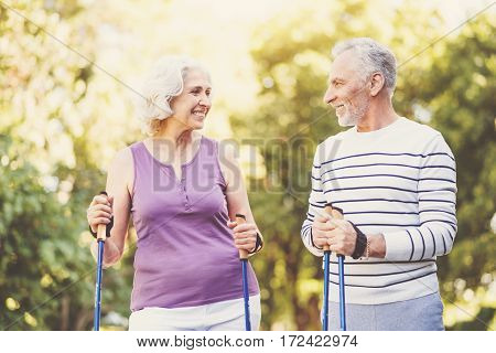 Many years together. Joyful pleasant senior couple looking at each other and smiling while practicing Nordic walking