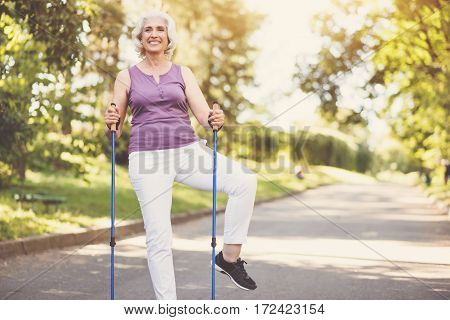 Morning workout. Cheerful pleasant senior woman holding walking poles and doing a physical exercise while having a morning workout in the park