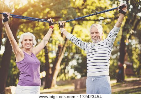 In the park. Nice joyful positive couple holding poles up above their heads and smiling while working out in the park