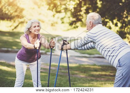 Senior couple. Cheerful nice elderly woman standing opposite her husband and smiling while exercising outdoors