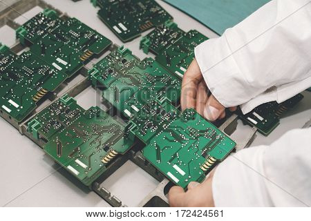 Technician with computer circuit board with chips. Spare parts and components for computer equipment. Production of electronics and maintenance.