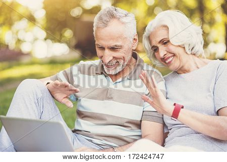 Distance communication. Nice pleasant aged couple sitting together in front of the laptop and saying hello to their children while speaking with them
