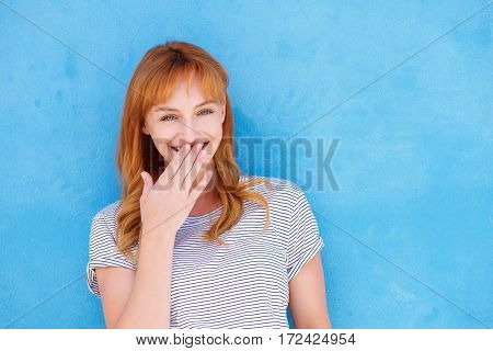 Happy Woman Laughing With Hand To Mouth Against Blue Wall