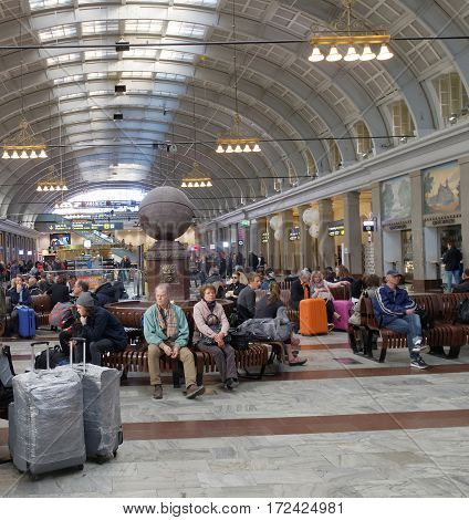 STOCKHOLM SWEDEN - MAY 05 2016: Lots of people waiting in the cental train station hall sitting on benches. May 05 2016 Stockholm Sweden