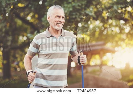 Care about health. Positive delighted aged man holding walking poles and smiling while enjoying his physical exercise