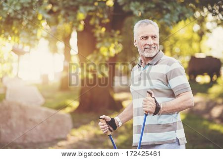 Wonderful mood. Sporty aged positive man holding poles and smiling while being in a wonderful mood