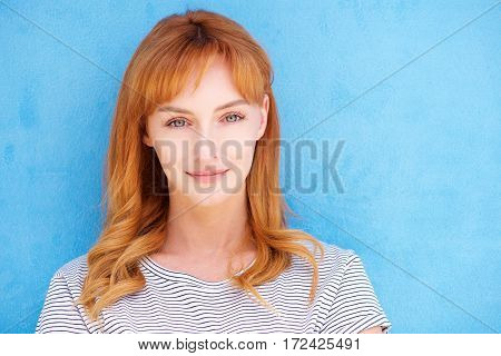 Attractive Young Woman With Red Hair Staring By Blue Wall
