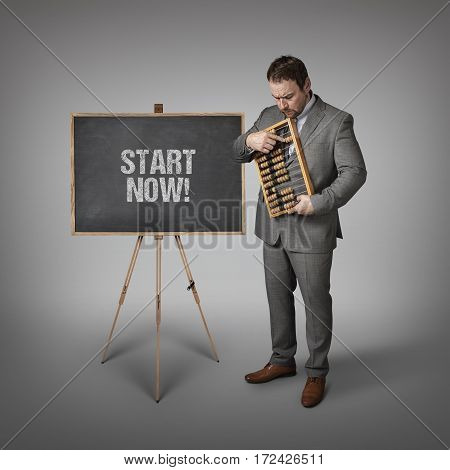 Start now  text on blackboard with businessman and abacus