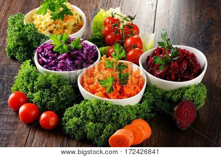 Composition With Four Vegetable Salad Bowls On Wooden Table