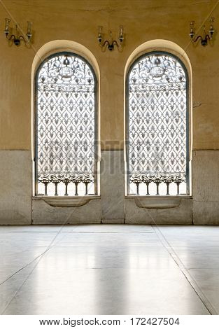 Cairo, Egypt - January 14 2017: Two iron ornate windows over stone wall and white marble floor at Sabil (Service providing free drinking water to pedestrians and animals) of Soliman Agha El-Selehdar
