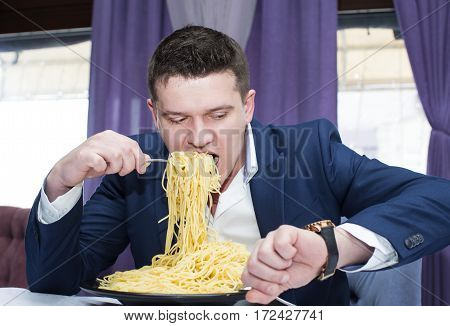 A man in a business suit eating spaghetti