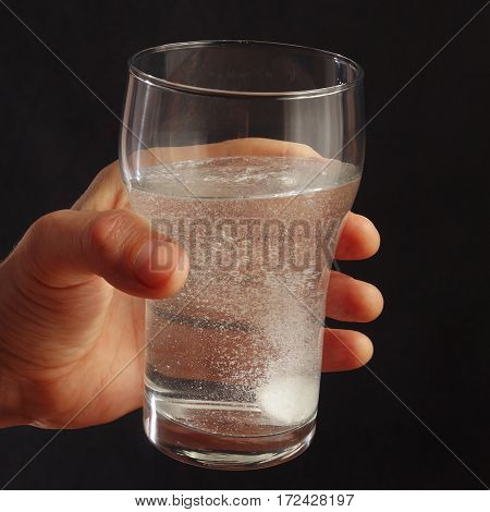 Hand with a glass of water and effervescent pill on a dark background.