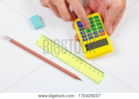 Hands calculate using a digital calculator over a workplace of the engineer