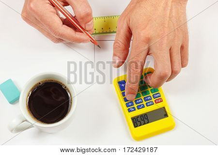 Hands compute using a pocket digital calculator over a workplace of the engineer