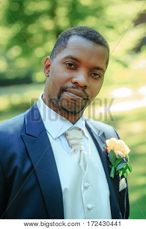 Handsome bearded man or african American groom in elegant suit coat with white tie and flower boutonniere for wedding ceremony poses on sunny summer day on natural background