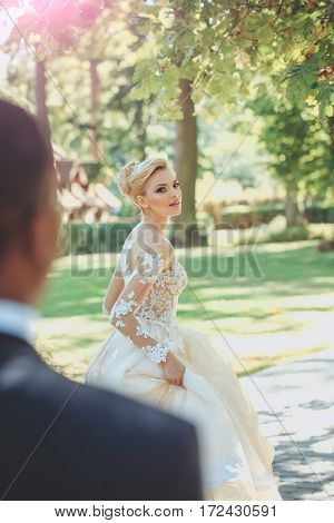 Pretty girl or cute bride with beautiful makeup and blond hair hairstyle in white sexy wedding dress with blurred african man or groom figure on sunny summer day outdoors on natural background