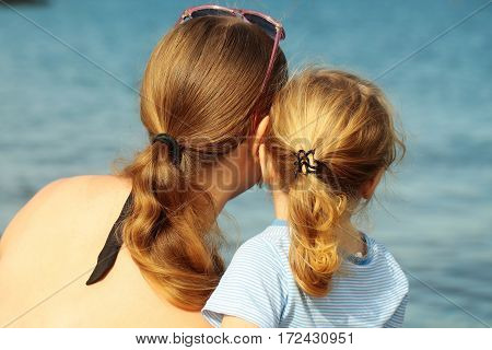 Mother and son beautiful woman and cute baby boy with blond hair ponytails look at sea or ocean water on sunny summer day on blurred blue background