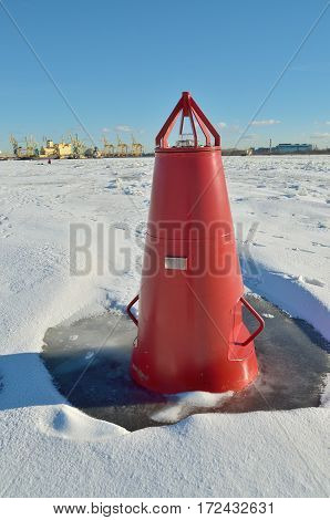 The red buoy on the frozen river.This luminous landmark for ships.