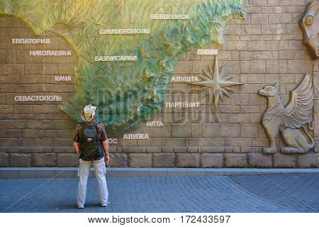 ALUSHTA. CRIMEA- September 10, 2015. Tourist standing in front of a decorative map of Crimea. Entrance to the park