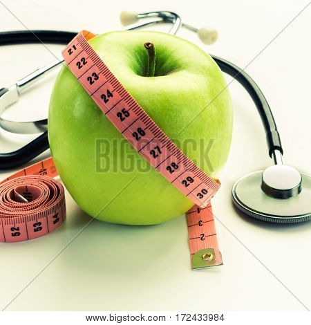 Losing weight - green apple measuring tape and stethoscope. isolated