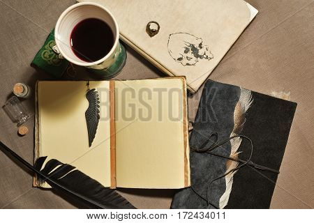 A mystical still life with old books, wineglass quill and charms