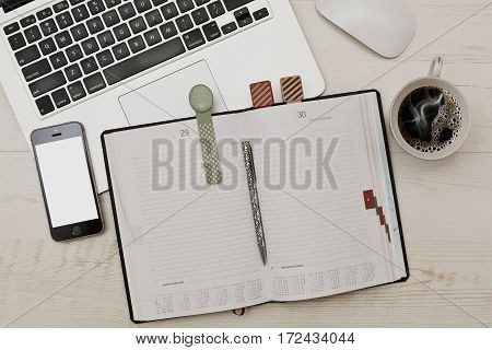 Some business accessories - diary with funny bookmarks laptop with a mouse cell phone and a cup of coffee on wooden table