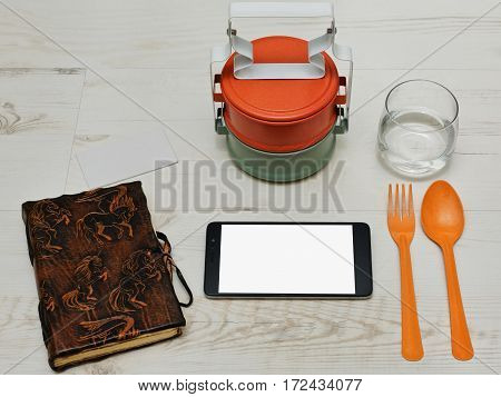 Lunch break with thai asian styled containers for meals tablet handmade diary and a glass of water