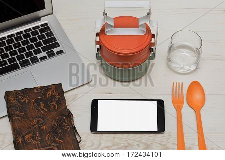 Everything is ready for the lunch on the workspace - asian styled food containers spoon and fork glass of still water and a cell phone for some internet browsing