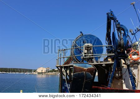 Industrial boat details with mechanisms, ropes, lifts with seaside marina background. Boat lifting mechanical devices in sea port.