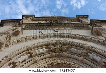 Lavishly decorated building facade arch. Old limestone building pattern with carved figures and ornaments. Limestone house view with blue sky.