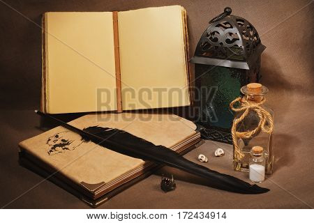 Mystical still life with vintage books with strange paintings old lantern antique pen wizard's ring and other witch's accessories
