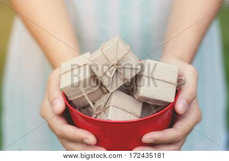 Woman hands holding gift boxes in red bucket on natural background Christmas and New Year concept. copy space.