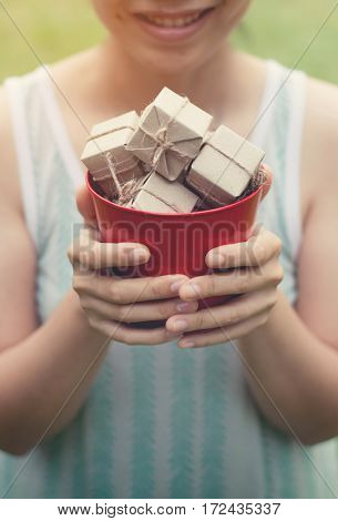 Woman smiling and holding gift boxes in red bucket on natural background Christmas and New Year concept. copy space.