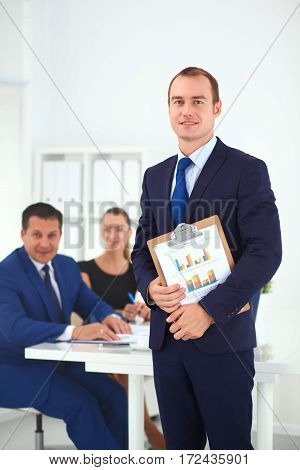 Portrait of a beautiful businessman standing in office with colleagues.