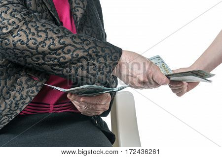 Grandmother gives part of packs of dollars his granddaughter, close-up, isolated on a white background