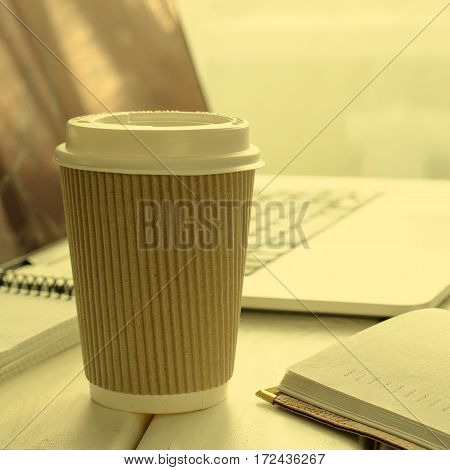 Paper cup of coffee on work-table with office stuff, notepad, laptop, pen and coffee cup, copy space, square, toned