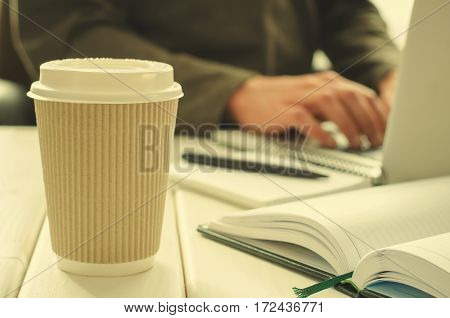 Paper cup of coffee on work-table with office stuff, notepad, laptop, pen, coffee cup and working man on background, horizontal, toned