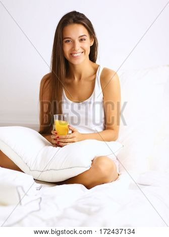 Beautiful young woman sitting in bed and having breakfast.