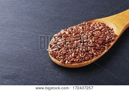 the brown flax seeds on a wooden spoon