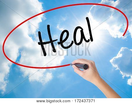 Woman Hand Writing  Heal  With Black Marker On Visual Screen