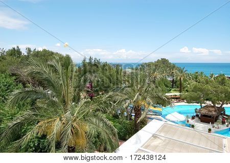 A view of a green garden a swimming pool a poolside bar and blue sea in the hotel of high class on the Mediterranean resort in Turkey.