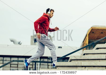 Handsome man running up at stairs with headphones