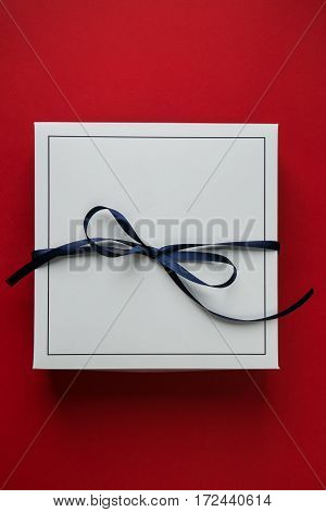 Single white gift paper box with blue ribbon bow, isolated on blue background.