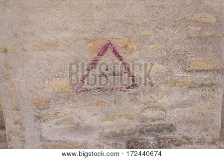 wall background with an old painted red arrow inside a triangular shape