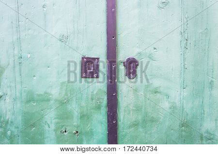 Green wooden door close up detail with rusty lock